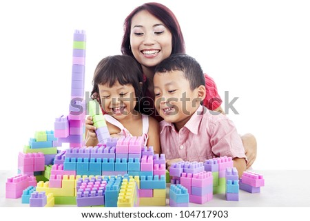 Happy siblings playing block with mother at home isolated on white - stock photo