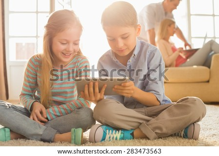 Happy siblings using digital tablet on floor with parents in background - stock photo