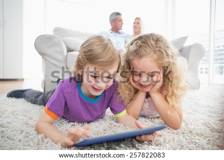 Happy siblings using digital tablet on rug while parents sitting on sofa at home - stock photo