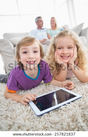 Happy siblings with digital tablet lying on rug while parents sitting on sofa at home - stock photo
