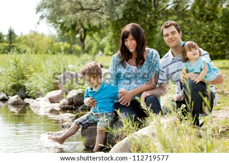 Happy similing young family sitting by lake - stock photo