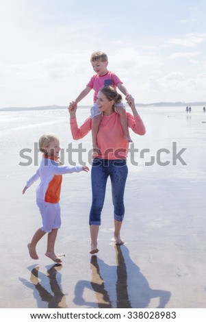 Happy single parent family walking along the beach. They are laughing and smiling and walking across the waters edge. The daughter is walking alongside her mother while her son is on her shoulders.  - stock photo