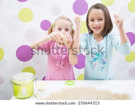 Happy sisters make cake in kitchen - stock photo
