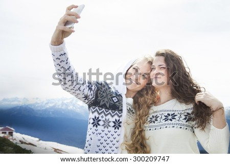 Happy sisters photographing a selfie in winter holidays with a snowy mountain in the background - stock photo