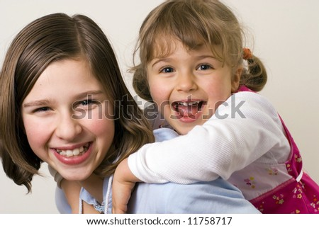 Happy sisters playing, piggyback - stock photo