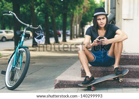 Happy skateboarder sitting on stairs. Young active people. Outdoors - stock photo