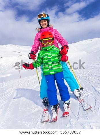 Happy skier boy with his sister enjoying winter vacation at ski resort - stock photo