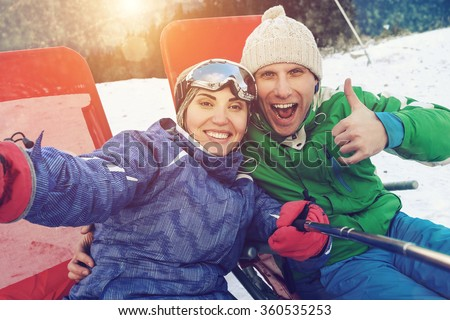 Happy skiers take a selfie photo on the top of mountain - stock photo