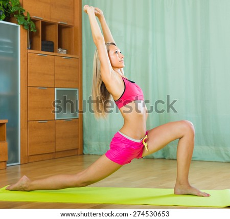 Happy slender young woman doing yoga at home - stock photo