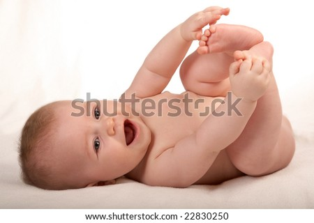 happy small baby isolated on white, playing with own legs - stock photo