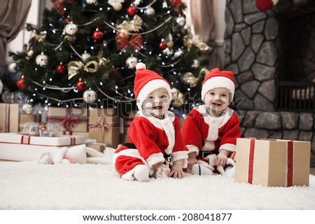 Happy small boys in santa hat with present have a christmas - stock photo