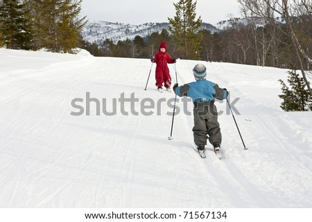 Happy small children meeting in the ski tracks - stock photo