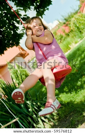 Happy small cute girl swinging on seesaw in garden behind family house - stock photo