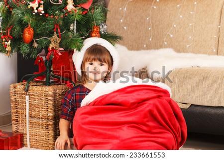 Happy small girl with Santa hat have a Christmas joy - stock photo
