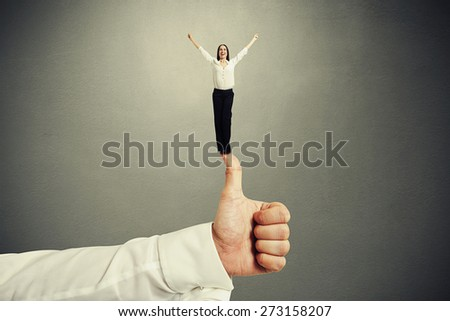 happy small woman standing on big thumbs up and raising her hands up over dark grey background - stock photo