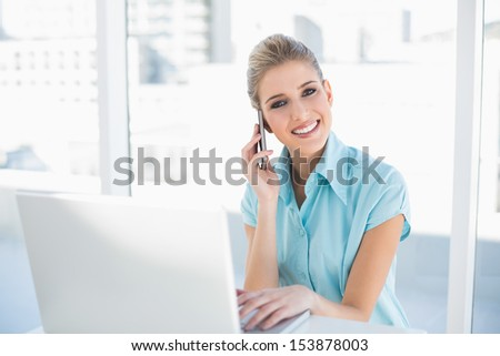 Happy smart businesswoman on the phone while using laptop in bright office - stock photo