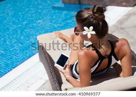 Happy smartphone woman relaxing near swimming pool listening with earbuds to streaming music. Beautiful girl using her mobile phone app 4g data to play songs while relaxing on summer luxury vacations. - stock photo