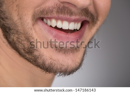 Happy smile. Cropped image of young men smiling while standing isolated on grey - stock photo