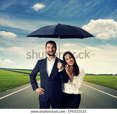 happy smiley couple under black umbrella at outdoor - stock photo