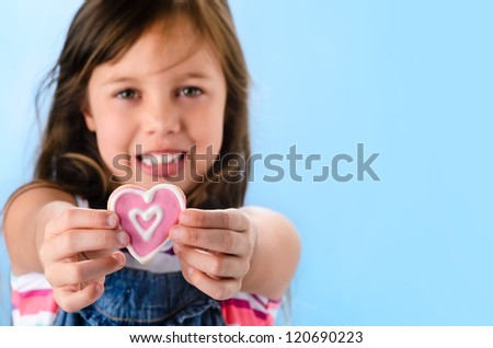 Happy smiling adorable young girl in denim dungarees holds out a pink heart shape cookie, selective focus on cookie, valentines or mothers day concept - stock photo