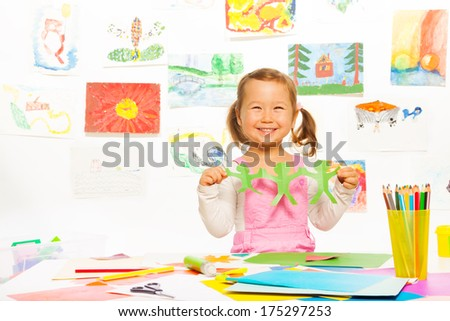 Happy smiling Asian girl holding paper green mans cut out - stock photo