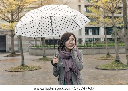 Happy smiling Asian woman holding an umbrella when rains stopped in city. - stock photo