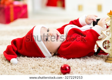 Happy Smiling baby boy lying on his back wearing Christmas Santa hat and suit - stock photo
