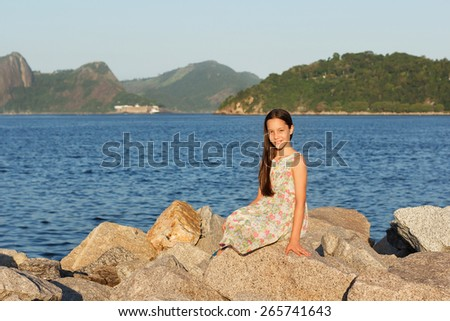 Happy smiling beautiful teen girl in dress with long brown hair sitting on stones on beach near sea. Selective focus. Toning effect - stock photo