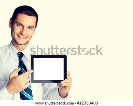 Happy smiling beautiful young businessman showing blank no-name tablet pc monitor, with copyspace area for slogan or text message, with copyspace area, posing at studio - stock photo