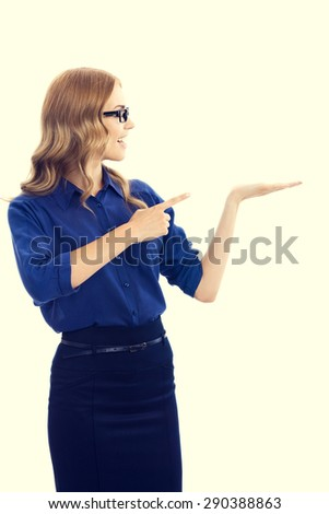 Happy smiling beautiful young businesswoman in blue clothing showing something or blank copyspace area for slogan or text message - stock photo
