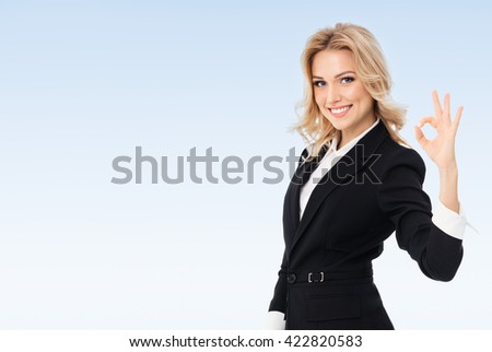 Happy smiling beautiful young businesswoman showing okay gesture, on blue background, with blank copyspace area for text or slogan - stock photo