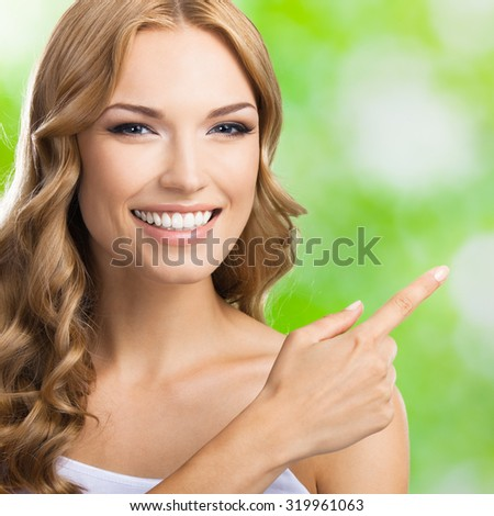 Happy smiling beautiful young lovely blond woman showing copyspace or something, outdoors - stock photo
