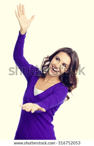 Happy smiling beautiful young woman carring, holding or showing something transparent or visual imaginary, in violet casual clothing - stock photo