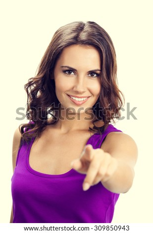 Happy smiling beautiful young woman in casual smart lilac clothing, showing copyspace, visual imaginary or something, or pressing virual button - stock photo