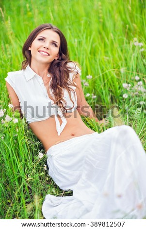 Happy smiling beautiful young woman lying among the grass and flowers - stock photo