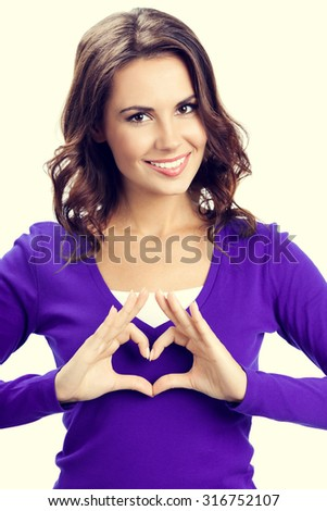 Happy smiling beautiful young woman showing heart symbol gesture, in violet casual clothing - stock photo