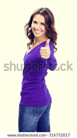 Happy smiling beautiful young woman showing thumbs up gesture, in violet casual clothing - stock photo
