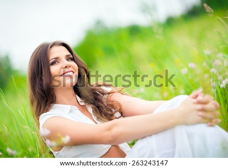 Happy smiling beautiful young woman sitting among the grass and flowers - stock photo