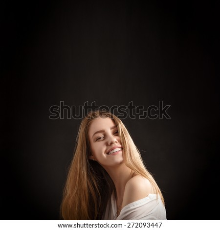 happy smiling blond girl on black background with copyspace - stock photo