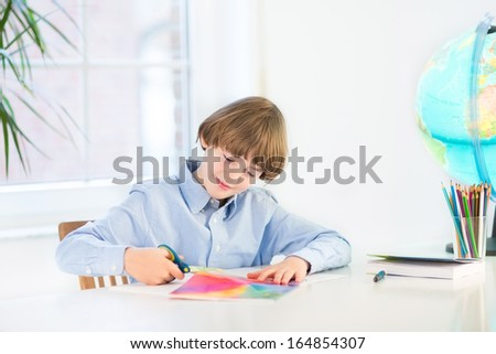 Happy smiling boy cutting colorful paper with scissors in a white desk - stock photo