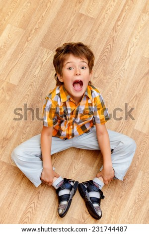 Happy smiling boy looking up at camera. Happy childhood. - stock photo