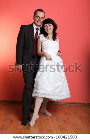 Happy smiling bride and groom on red background - stock photo