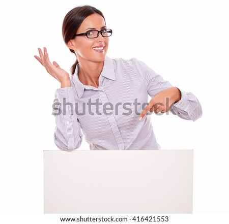 Happy, smiling brunette businesswoman looking at the camera holding a blank placard and pointing at it, wearing her straight hair tied back and a button down shirt on a white background - stock photo