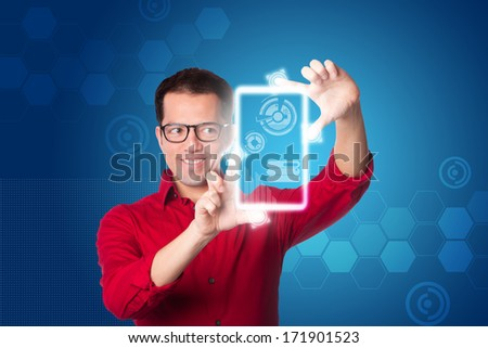 Happy smiling Business man in red shirt looking at digital graph chart on hologram touch screen computer tablet device, on blue. - stock photo
