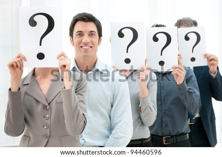 Happy smiling business man standing out of the crowd with other people hiding their face behind a question mark sign. - stock photo