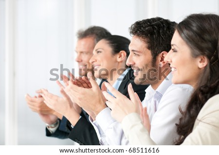 Happy smiling business team clapping hands during a meeting in office - stock photo