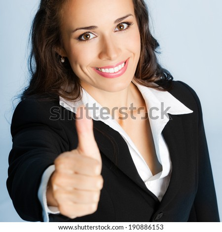 Happy smiling business woman showing thumbs up gesture, over blue background - stock photo