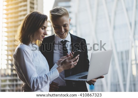 Happy smiling businessman and businesswoman using laptop and smartphone while working on new project, two young professional employers working on portable computer discussing project of constructions - stock photo