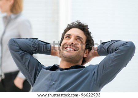 Happy smiling businessman looking up with dreaming expression at office - stock photo