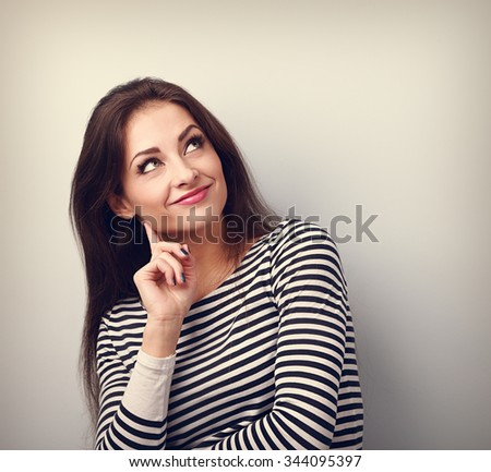 Happy smiling casual woman thinking and looking up on empty copy space. Toned portrait - stock photo